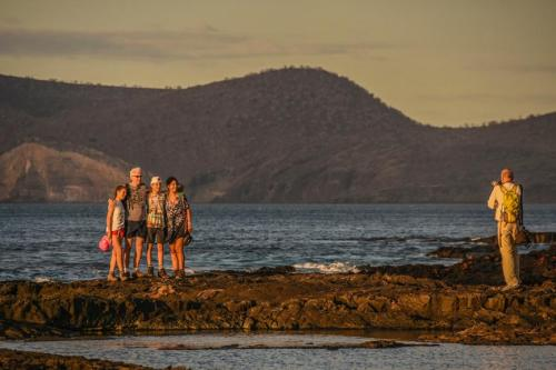 Family taking a picture of Galapagos' sunset.